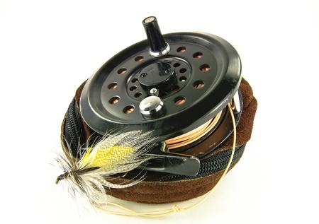 플라이 피싱 릴 (Fly Fishing Reel) : 잘 사용 된 낚시 릴은 가죽 케이스 위에 플라이 낚시 용 루어와 함께 앉습니다.