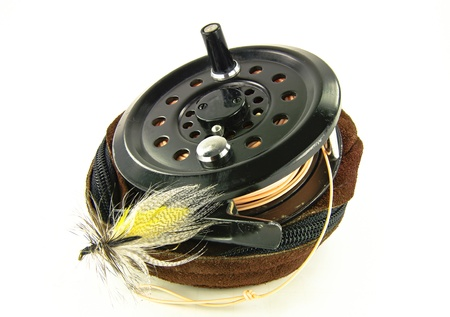 trout fishing: Fly Fishing Reel:  A well-used fishing reel sits atop its leather case along with a lure made for fly-fishing.