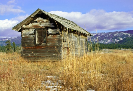 Deserted Cabin:  An old wooden cabin, falling to ruin, stands on a grassy hillside.
