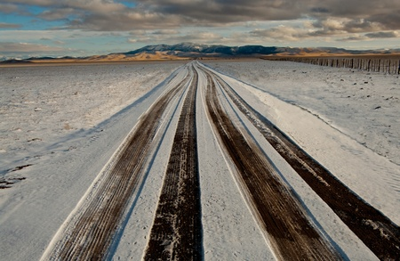 Snowy Road: Tire tracks show through light snow on a long, straight road in western New Mexico. photo