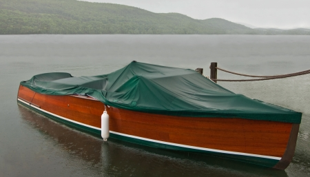 showers: Covered Boat in the Rain:  A canvas top protects a small wooden boat during spring rain showers.