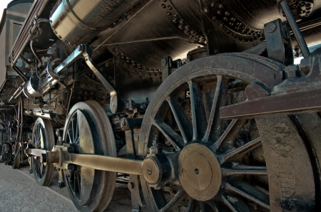 Locomotive:  A large boiler rests on the heavy iron wheels of an old steam locomotive. photo