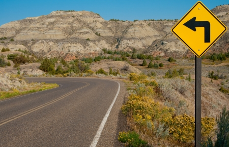 warns: Left Turn Sign:  A road sign warns of a sharp left turn on a narrow road through Theodore Roosevelt National Park in southwest North Dakota. Stock Photo