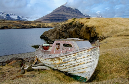 Old Fishing Boat:  A small, weathered boat rests on a remote shore in eastern Iceland. photo