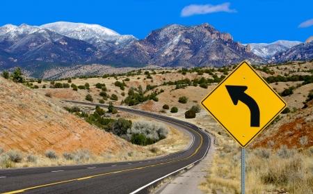 Curva de la señal de peligro: Una señal de tráfico alerta a los conductores a una carretera de montaña en la curva norte de Nuevo México. Foto de archivo