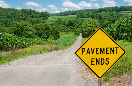 warned: Pavement Ends Sign   Motorists are warned of a change from asphalt to gravel on a country road in northern Maryland  Stock Photo