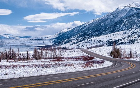 Sierra Nevada Highway in Winter   A scenic California highway curves beside snowy mountains and a frozen lake near Yosemite National Park  photo