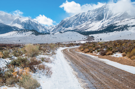 Desert Mountain Road in Winter   A dirt road wet with melting snow leads across a desert plain toward the Sierra Nevada Mountains near Yosemite National Park  photo