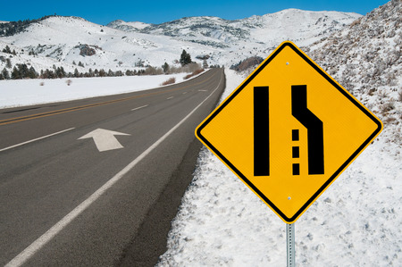 Merging Lanes Sign   Motorists are warned to move left as the right lane ends along a mountain road   photo