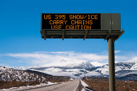 Road Conditions Sign    A lighted message warns travelers to prepare for hazardous driving conditions on a Sierra Nevada mountain road  Stock Photo
