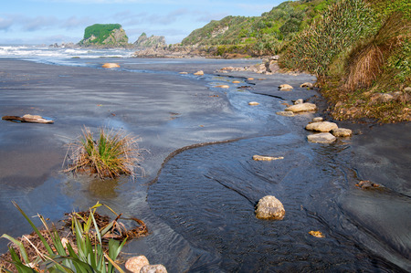 watershed: Small Stream Flowing Into the Sea    A fresh water stream reaches the Tasman Sea on the west coast of New Zealand's South Island  Stock Photo