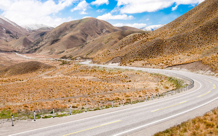 New Zealand Desert Mountain Pass   A two lane highway curves through arid terrain toward Lindis Pass on New Zealand�s South Island  photo