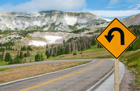 warns: U-Turn Sign:  A sign warns motorists of a sharp bend ahead on a mountain road in southern Wyoming. Stock Photo