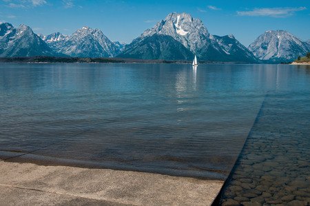 Boat Launch Ramp:  Shallow waves reach a concrete ramp that slopes gradually into Jackson Lake in Grand Teton park Stock Photo