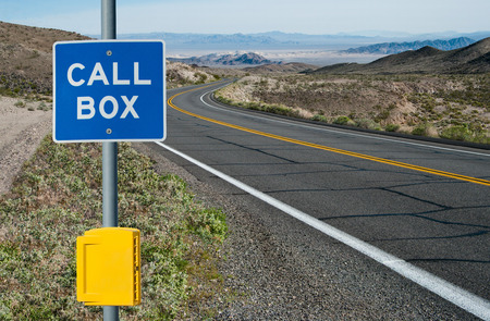 informs: Emergency Call Box and Sign:  A sign informs motorists of telephone assistance available on a desert highway in California. Stock Photo
