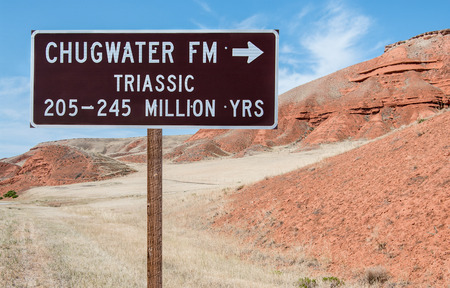 identifies: Geological Information Sign:  A road sign identifies the type and geological period of a rock formation in northeast Wyoming.