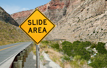 informs: Rock Slide Area Warning Sign:  A sign informs motorists of a rock slide area ahead on a mountain road in northeast Wyoming.
