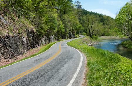 smoky mountains: North Carolina Byway:  A narrow road curves past a quiet stream and rocks wet from the flow of underground springs in the North Carolina foothills of the Smoky Mountains.