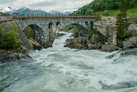 rushing water: Bridge Over Rough Water:  A bridge made of heavy stone blocks stands above a whitewater river in the mountains of southwest Norway.