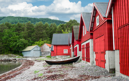 fishing hut: Boathouses in Norway:  A wooden boat sits in front of a row of boathouses on the shore of a fjord in southwest Norway.