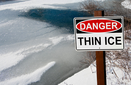 warns: Thin Ice Warning Sign:  A sign warns of danger as ice thaws on a pond in southern Wisconsin. Stock Photo