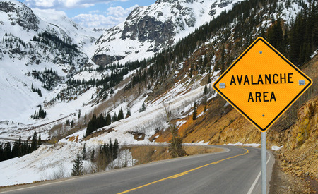 warns: Avalanche and Sign:  A sign warns motorists in an area of southwest Colorado where an avalanche has recently covered the road.