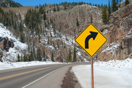warns: Right Curve Sign:  A sign warns of a right turn ahead on a mountain road in southern Colorado.