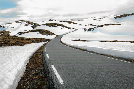 backroad: Snowfields Road in Norway:  A narrow road winds through a snowy mountain pass in southwest Norway. Stock Photo