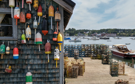 buoys: New England Lobster Fishing Dock:  Marker buoys for lobster traps decorate the side of a fishing shack on a wharf in Maine. Stock Photo