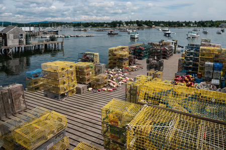 Lobster Traps on a Fishing Dock in Maine:  Stacks of lobster pots cover a wooden pier on a bay in New England.