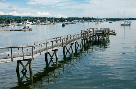 extends: Long Pier:  A wooden walkway extends far across the shallow end of a bay in Maine.