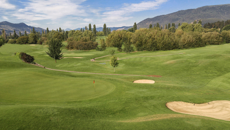 Mountain Golf Course:  Rolling green hills and mountains create an attractive setting for golf on a sunny day in British Columbia. Stock Photo