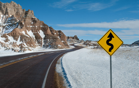 warns: Sharp Curves Warning Sign:  A sign warns of a twisting road ahead on a winter day in Badlands National Park. Stock Photo