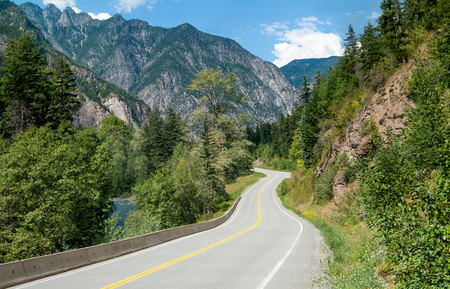 Scenic Road in British Columbia:  A winding tree-lined road passes a stream and rocky outcroppings in its climb through the mountains northeast of Vancouver, Canada.