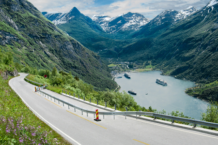Fjord Road in Norway:  A two-lane road narrows as it descends beside Geirangerfjord in the mountains of southwest Norway.