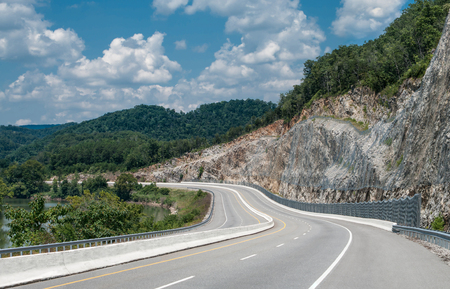 Appalachian Mountain Highway:  A four lane divided highway curves between a winding river and a steep cut rock face in eastern Tennessee. Stock Photo