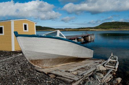 Boat on a Wooden Ramp :  A weathered fishing boat sits on a handmade ramp for launching into a bay on the west coast of Newfoundland.