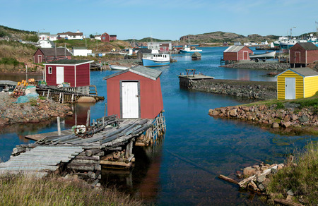 Newfoundland Fishing Village:  Fishing shanties sit on rustic wooden piers and rock jetties that extend into a small harbor on the north coast of Newfoundland. Stock Photo
