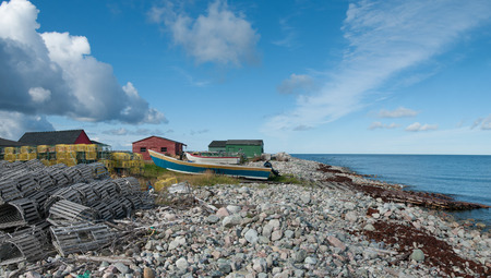 Lobster Boats on a Rocky Beach in Newfoundland:  Small fishing boats sit on wooden launch ramps amid stacked lobster traps on the rocky western coast of Newfoundland.