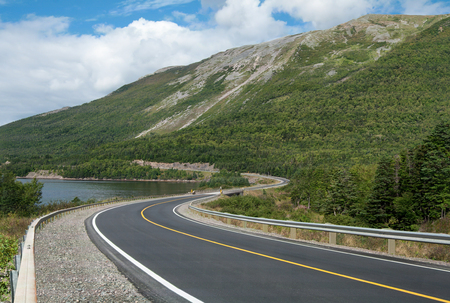 Scenic Road in Newfoundland  Description:  A two-lane highway curves past an ocean inlet and climbs into a mountainous area in Gros Morne National Park on the west coast of Newfoundland. Stock Photo