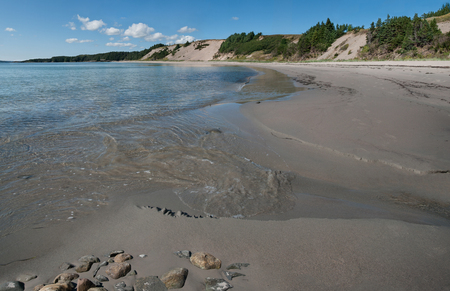 Sandy Beach in Newfoundland:  Gentle waves from the Atlantic Ocean meet the flow of a small stream at Sandy Cove Beach on the eastern shore of Newfoundland. Stock Photo