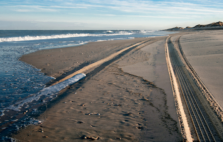 Beach Drive:  Evening shadows and an incoming tide fill the tracks of an off-road vehicle along the edge of Cape Hatteras National Seashore.