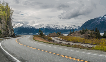 Alaska Scenic Road: The Seward Highway curves beneath cloudy skies as it passes by snow-covered mountains at the edge of an ocean inlet south of Anchorage.