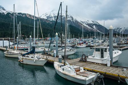 Alaska Harbor:  Fishing boats and sailing yachts dock in the harbor at Seward, Alaska on a cloudy day in May.