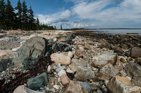 Natural Seawall:  Boulders, small rocks and gravel collect against granite formations to create a sea barrier on the southwest corner of Acadia National Park. Stock Photo