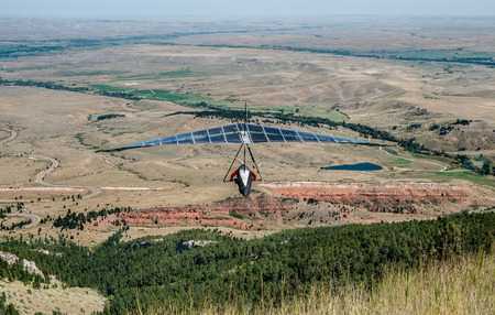 Hang Gliding in Wyoming:  A glider sails over the landscape of northeast Wyoming after launching from a roadside cliff in the Big Horn Mountains. Stock Photo