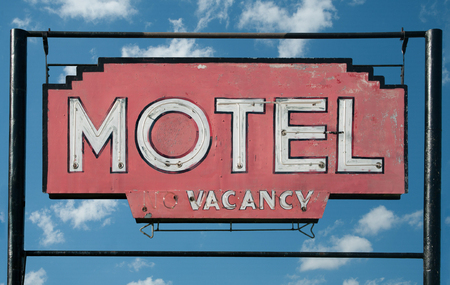 Motel Sign:  A weathered sign invites travelers to stop at a small motel in rural Minnesota.