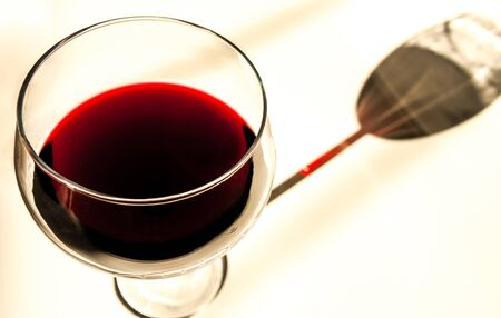 Wine Glass: A glass of red wine casts a tinted shadow on a white tablecloth.