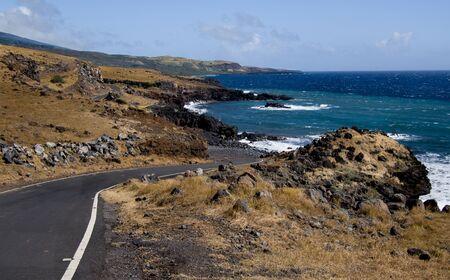 Maui South Coast Highway:  A narrow road curves through arid terrain along a volcanic shoreline as the Piilani Highway approaches the eastern end of Maui. 免版税图像