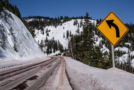 Left Curve Sign:  Motorists are warned of a sharp turn ahead on a snowy mountain road in Montana.